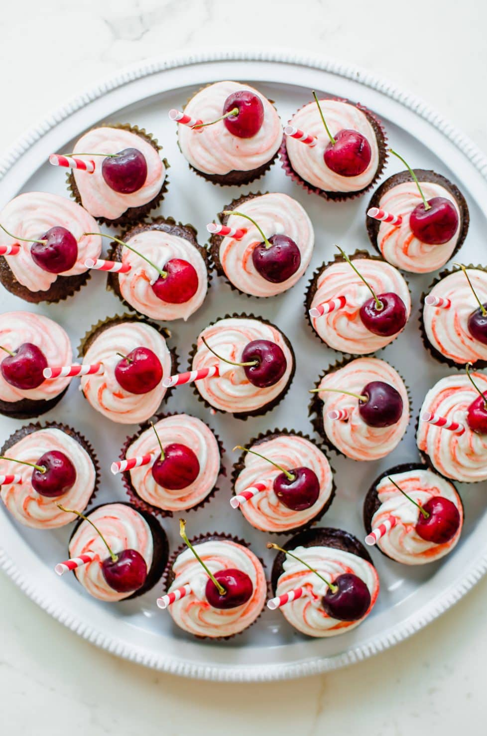 An overhead shot of a large platter of chocolate cupcakes topped with red striped frosting, a cherry, and a red striped paper straw.
