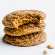 A stack of pumpkin cookie butter doodle cookies with a bite taken out of the top cookie.