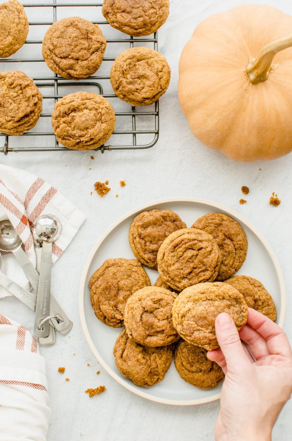 A hand reaching to grab a cookie from a plate of Pumpkin Cookie Butter Doodles with a pumpkin on the side.
