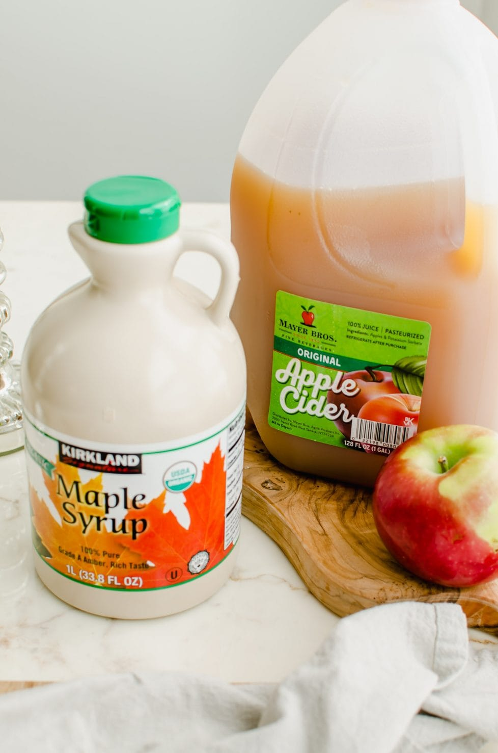 A jug of apple cider, bottle of maple syrup, and an apple sitting on a cutting board.