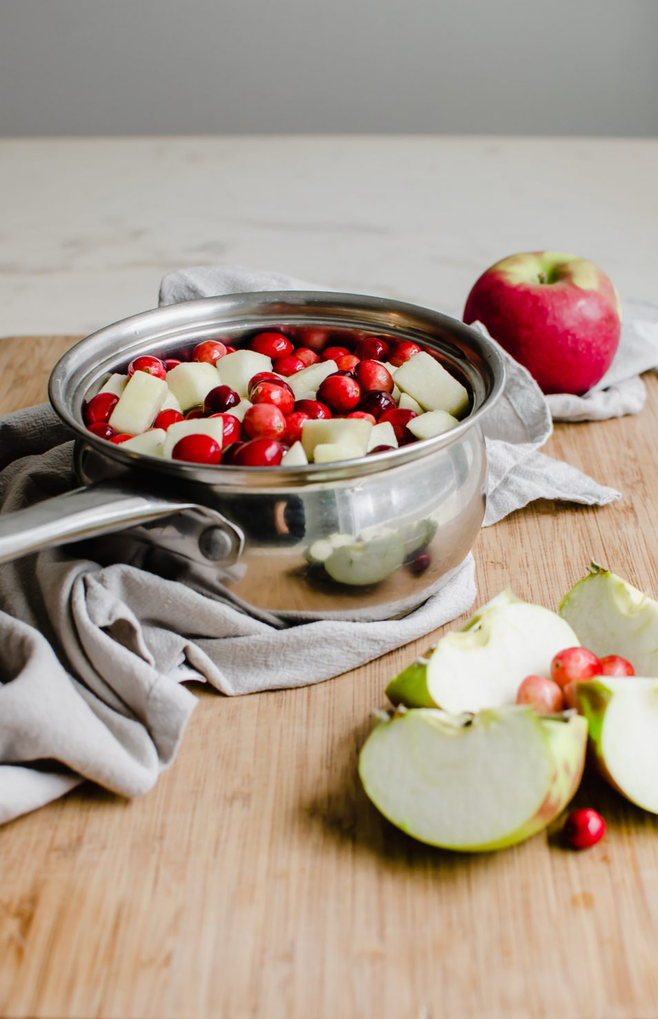 A saucepan with fresh cranberries and sliced apple sitting on a cutting board with a grey dish towel underneath.