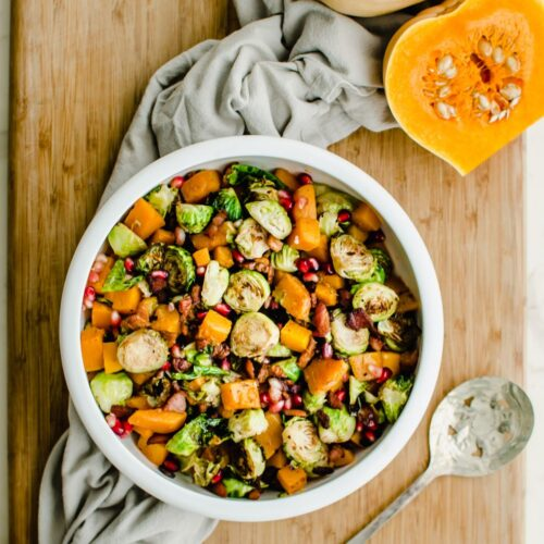 A white bowl filled with roasted brussels sprouts and butternut squash with a cut butternut squash half on the side.