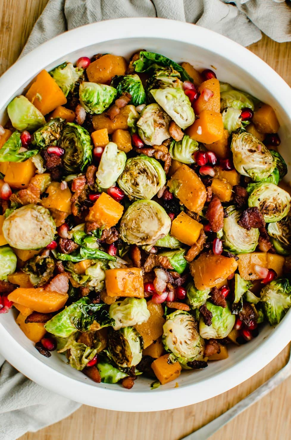 A close-up overhead shot of a white bowl filled with roasted brussels sprouts, butternut squash, and pomegranate arils.