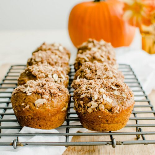 A cooling wire rack with pumpkin cream cheese streusel muffins and a pumpkin in the background.