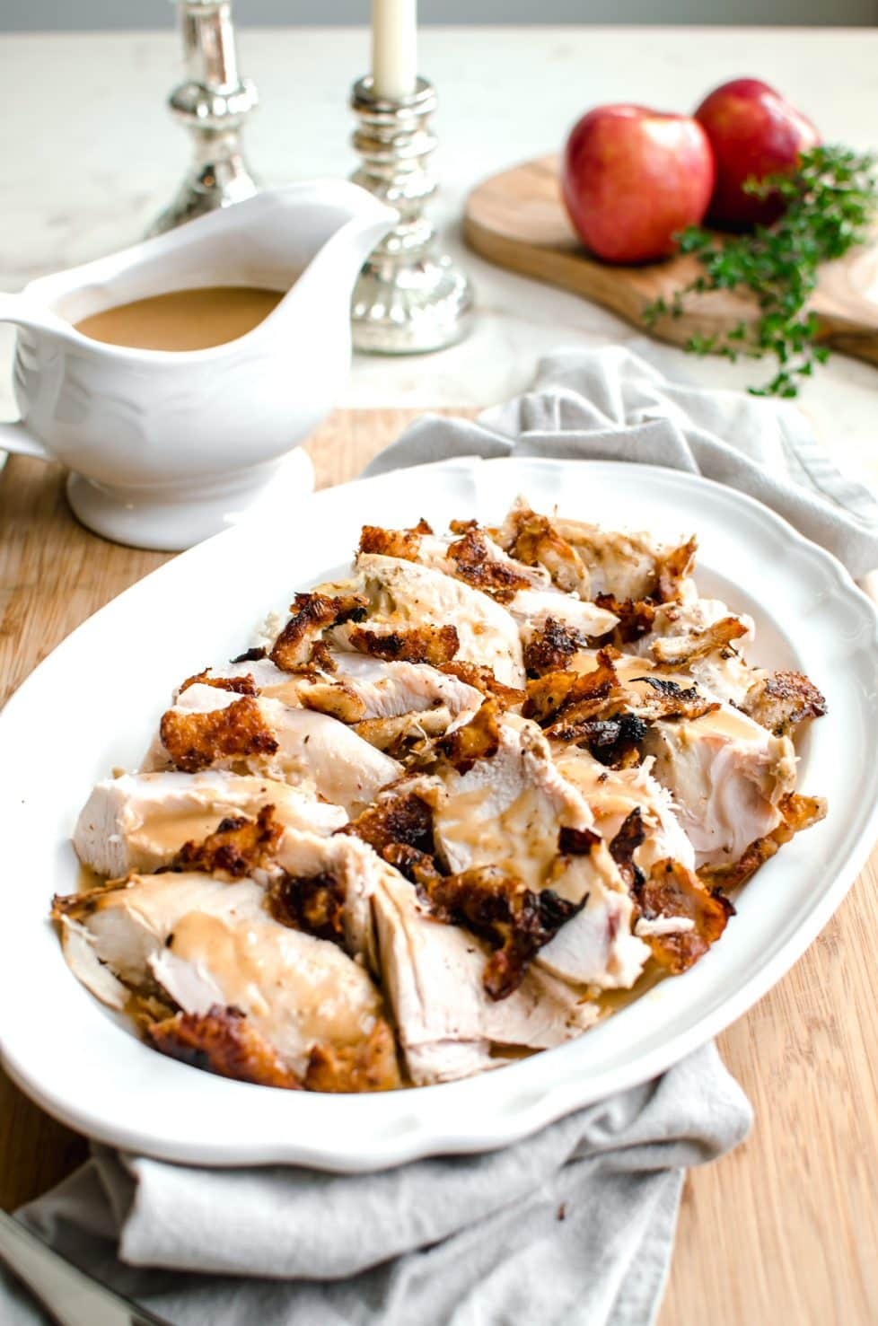 A white platter with sliced turkey next to a gravy boat.