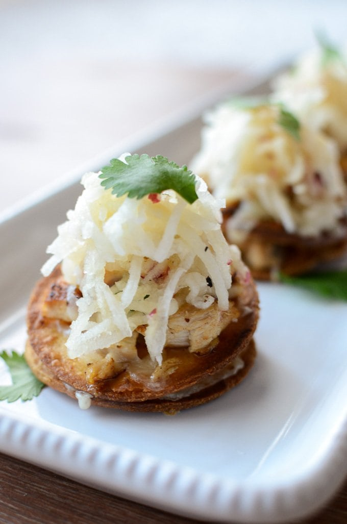 A close-up shot of mini chicken tostadas on a white platter garnished with slaw and cilantro.