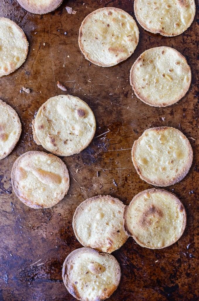 Mini crispy tostada rounds on a baking sheet.