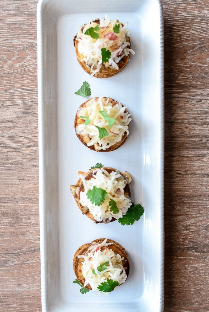 A row of mini Chicken Tostadas garnished with slaw and cilantro on a rectangular white serving platter.