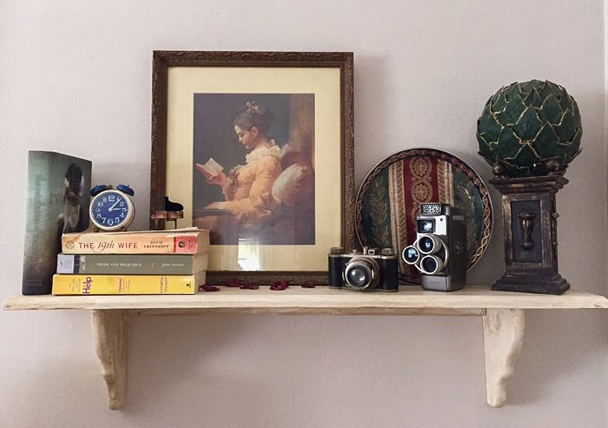 This shelf features a collection of vintage cameras, old books, and some decor odds and ends from Poppy's house www.sweetcayenne.com