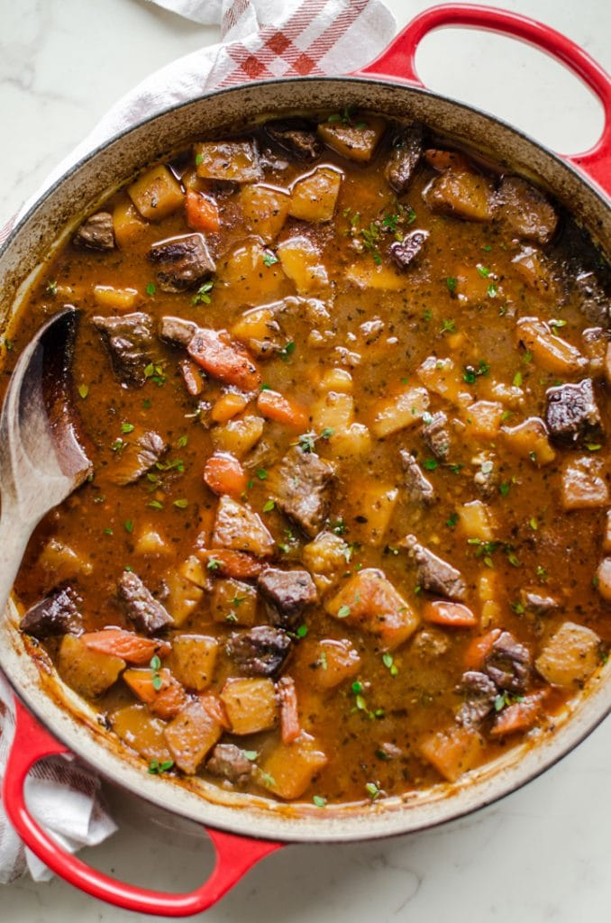 Beef Stew in a cast iron braiser with a wooden spoon.
