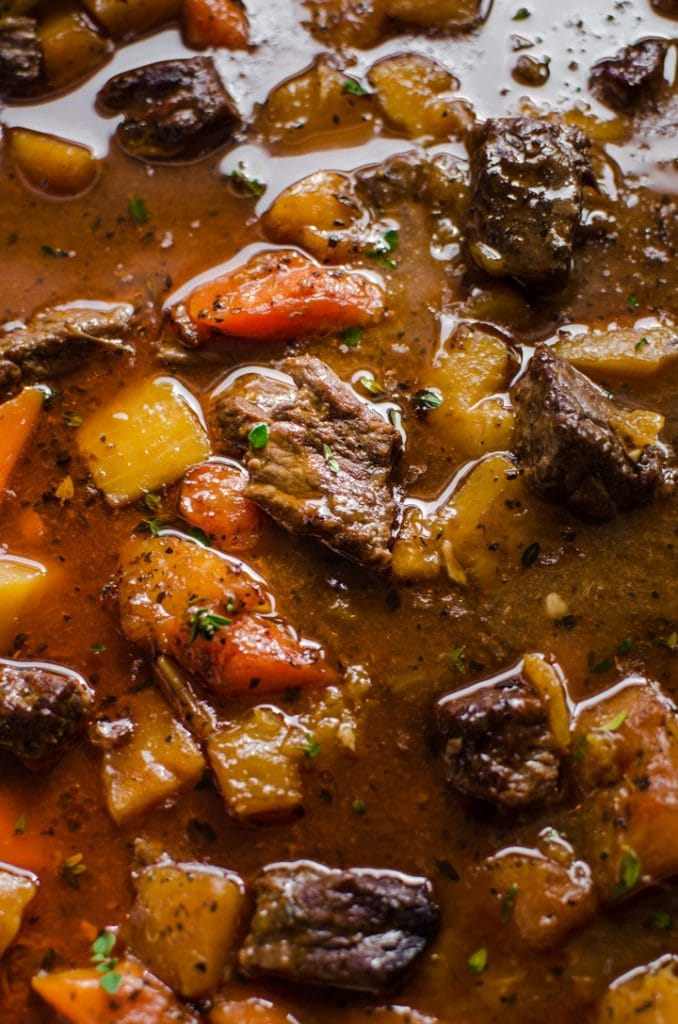A close up shot of beef stew inside of a pot.