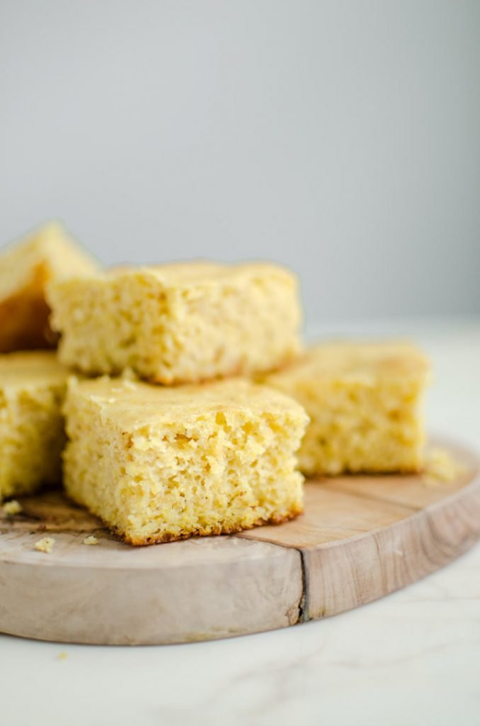 Squares of cornbread on an olive wood cutting board.