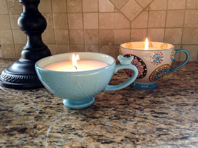 Coffee Cup Candles lit on a marble kitchen counter.