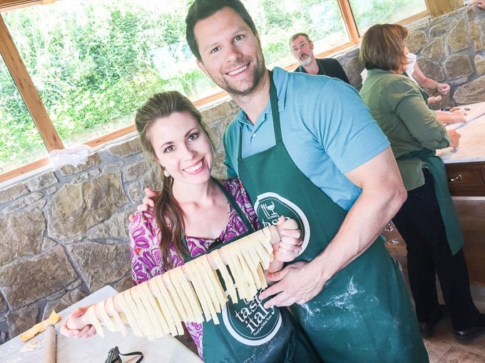 A young woman and man holding up a rolling pin with drying fresh pasta.