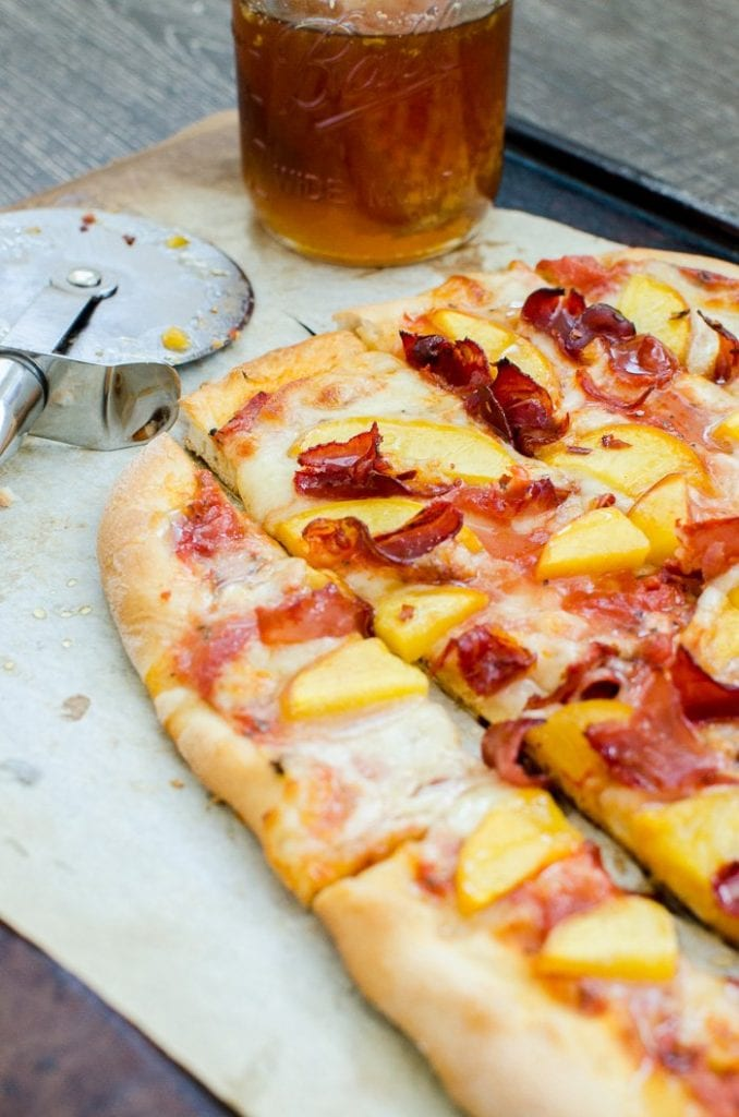 Peach prosciutto pizza sliced and with a glass of tea.