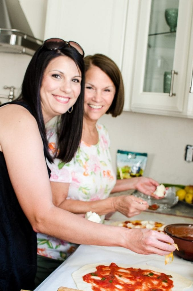 Two women topping pizzas.
