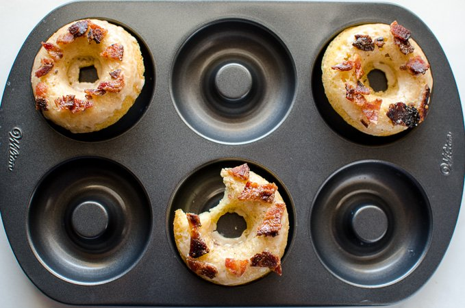 Maple Bacon Donuts are baked, not fried, for a lower-fat but delicious indulgence. Dipped in a brown butter maple glaze and crispy pieces of candied bacon!