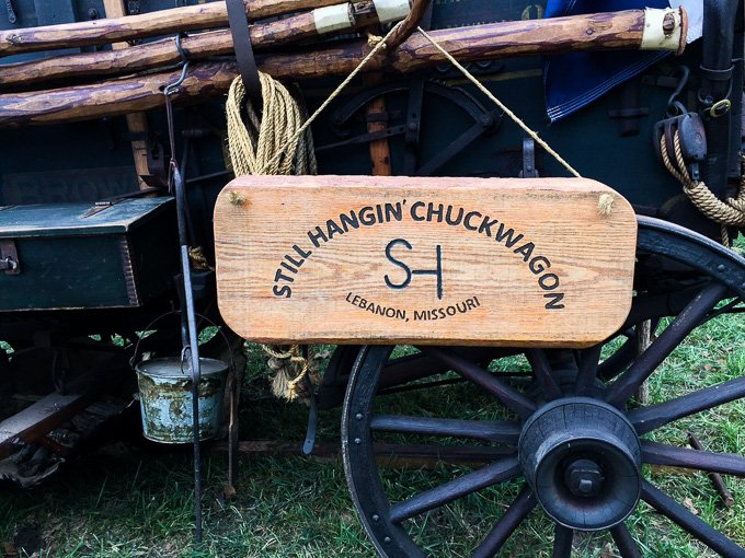 A chuck wagon with a wooden sign.