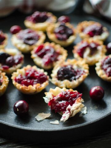 A tray of cranberry brie tartlets with fresh cranberries on the side.