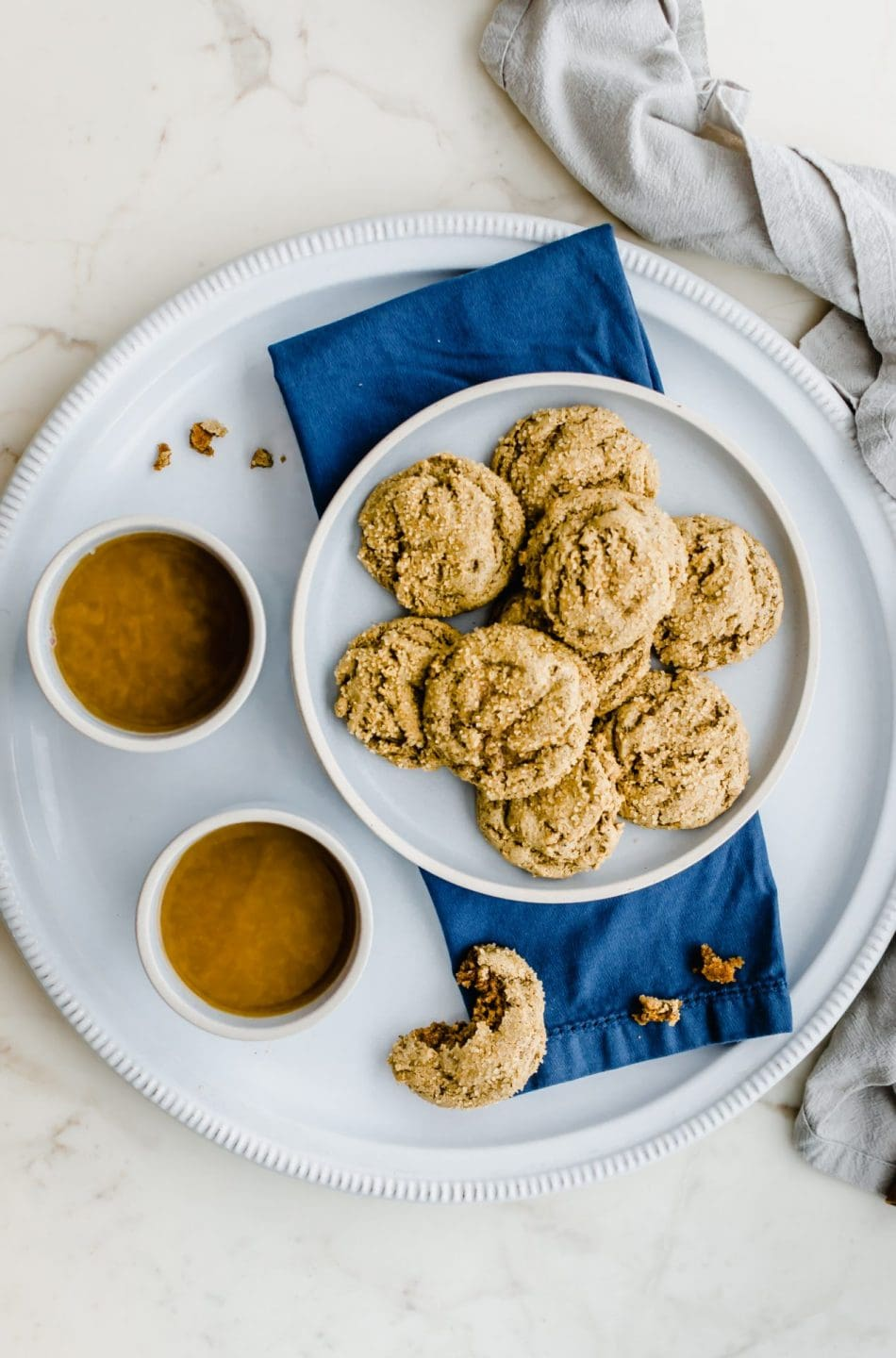Two blue stone cups of spiced tea on a white platter with a plate of ginger cookies on the side.