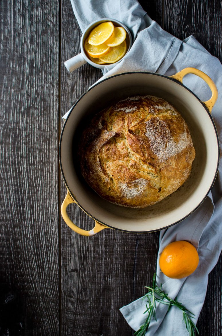 A yellow Dutch oven with a bread boule inside sitting on a grey towel with a bowl of meyer lemons on the side.