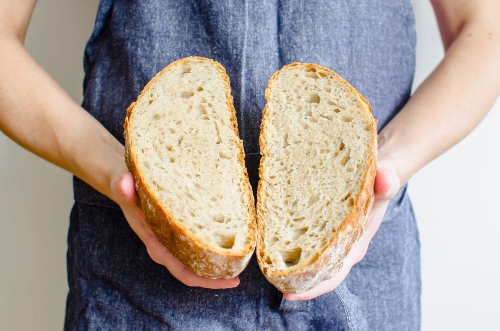 A women's hands holding a bread boule broken in half.