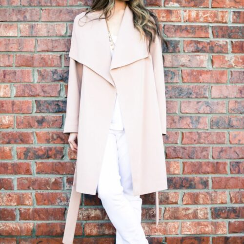 A chic spring look featuring a neutral color palette of a blush trench coat, white blouse, white jeans, and taupe sandals. Style and fashion inspiration for women.