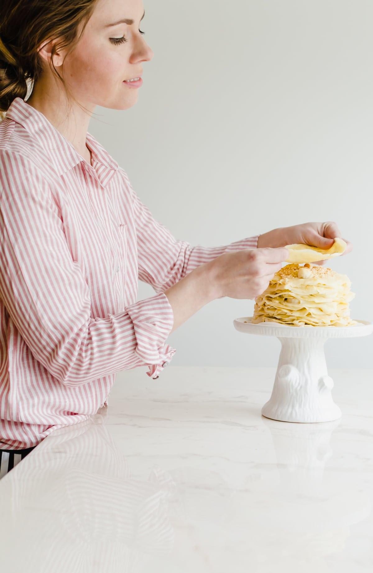 A girl placing a crepe layer on a banana pudding crepe cake.