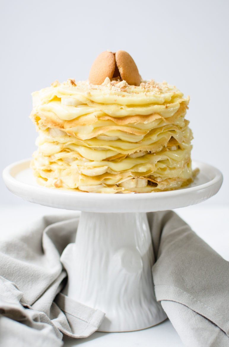 Straight-on shot of a crepe cake with layers of banana pudding, sliced bananas, and Nilla wafers on top of a white ceramic cake stand against a white background.