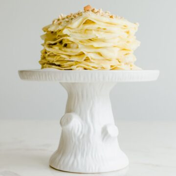 A banana pudding crepe cake on a white cake stand against a white background.