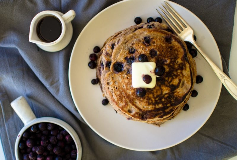 Overhead picture of pancakes with butter and blueberries.
