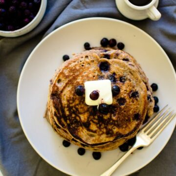 Overhead picture of a stack of blueberry pancakes with butter on them.