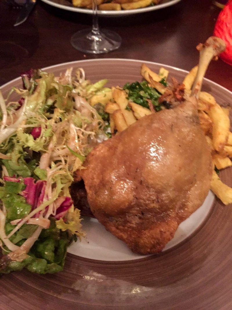 Crispy duck leg with a fresh salad and garlic parsley frites in Paris, France