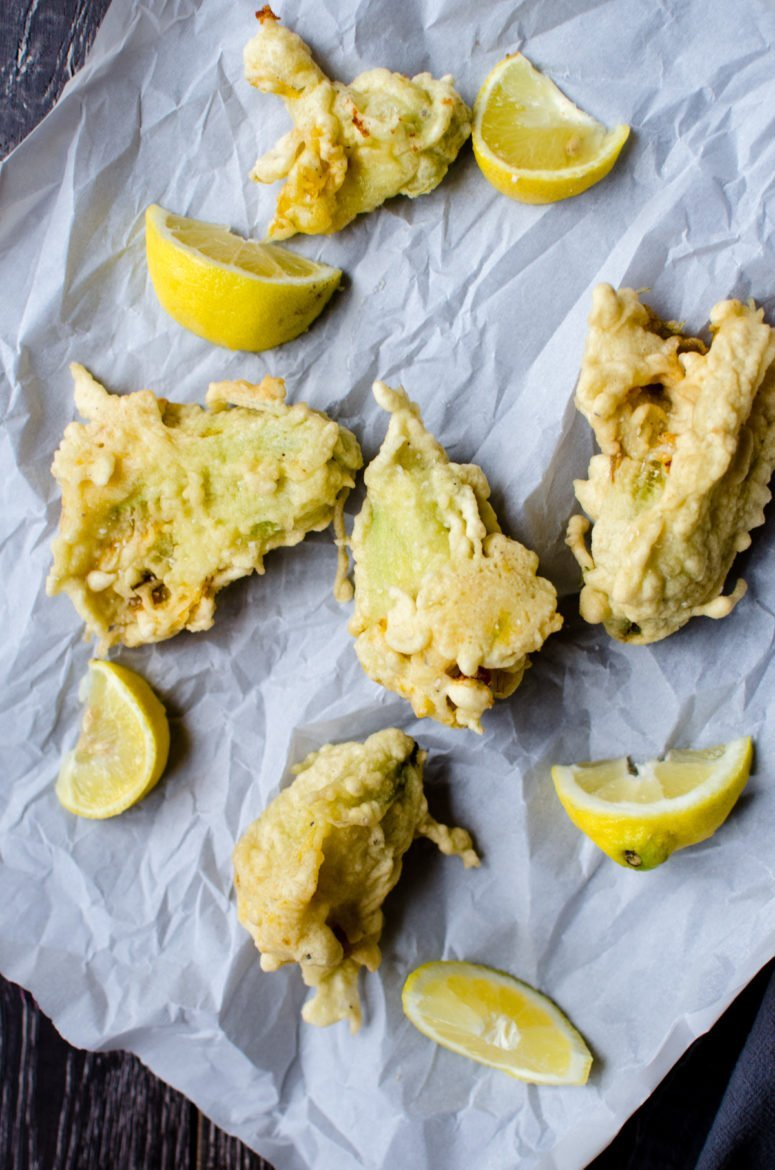Fried zucchini blossoms on parchment paper with lemon wedges.