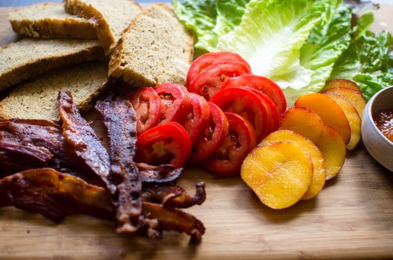 Sliced ingredients for BLT sandwiches on a cutting board.