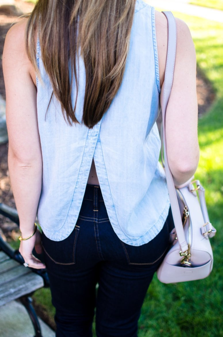 A chic and sophisticated denim on denim look that's perfect for fall transition fashion. High waisted jeans in a dark wash with an open-back chambray shirt.