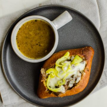 An overhead shot of an Italian beef sandwich on a grey plate with a cup of au jus on the side.