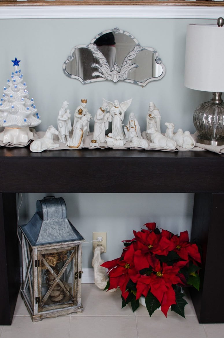 Our entry Christmas decor includes a white porcelain manger set from my Grandmother, a vintage light up Christmas tree, and a lovely poinsettia.