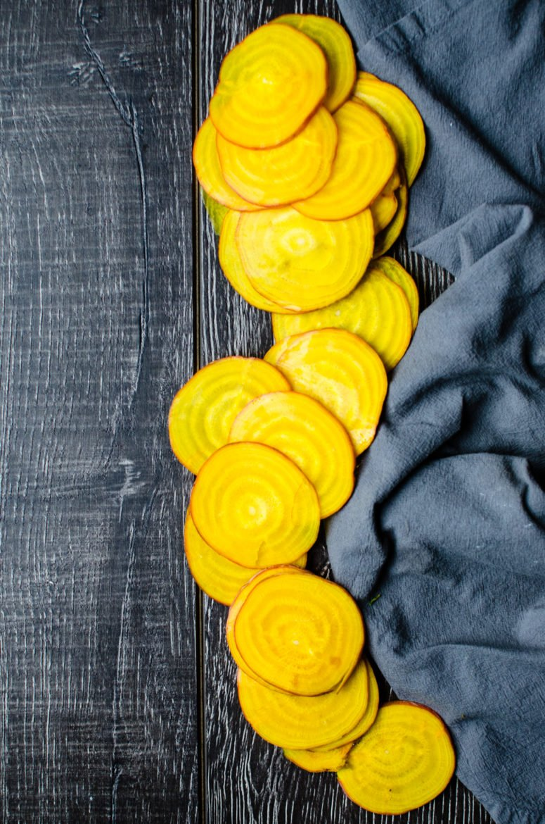 Thin slices of yellow beet on a blue dish towel.