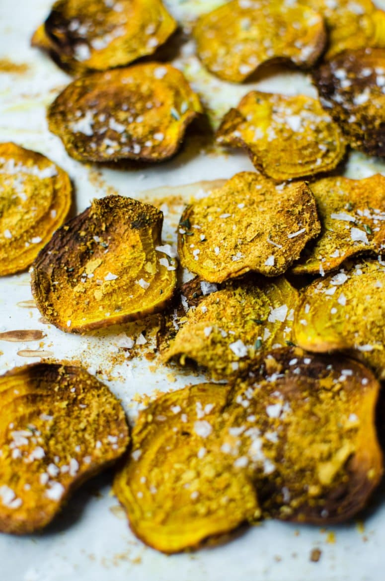 A close up shot of crispy beet chips with cheese seasoning and sea salt flakes.