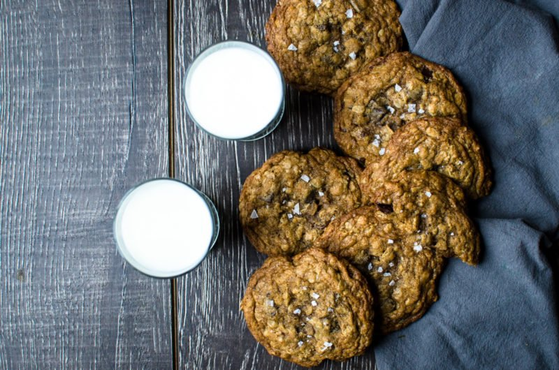 Two cups of milk seen with 6 cookies.