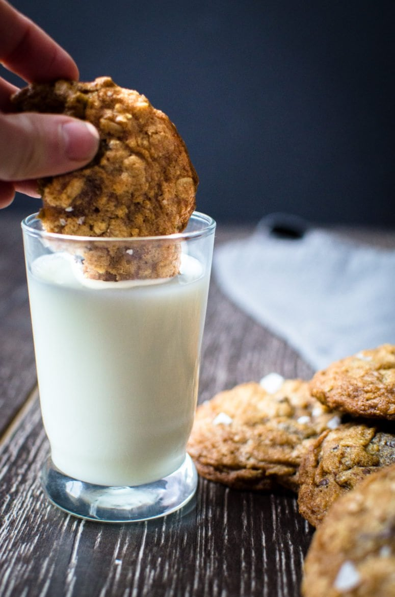 Chocolate chip cookie being dipped in milk.