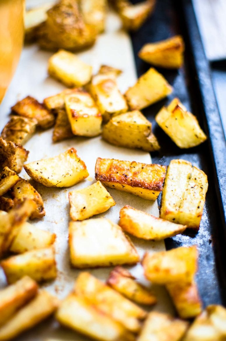 Crispy potatoes on a cooking tray, side view.