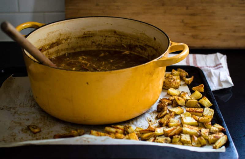 Side view of a pot of gumbo and a tray of crispy potato pieces.