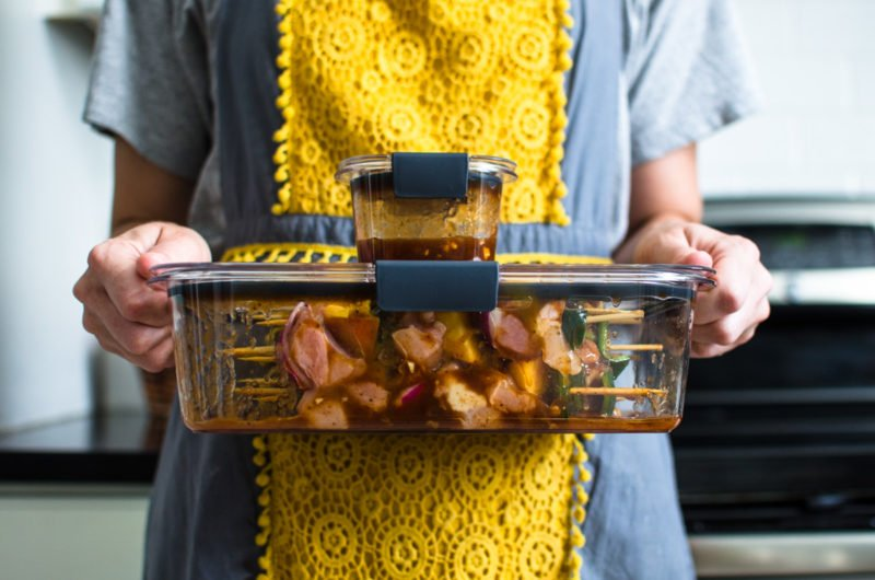 A woman with a grey and yellow apron holding two Rubbermaid Brilliance containers with Peach BBQ chicken kabobs inside.
