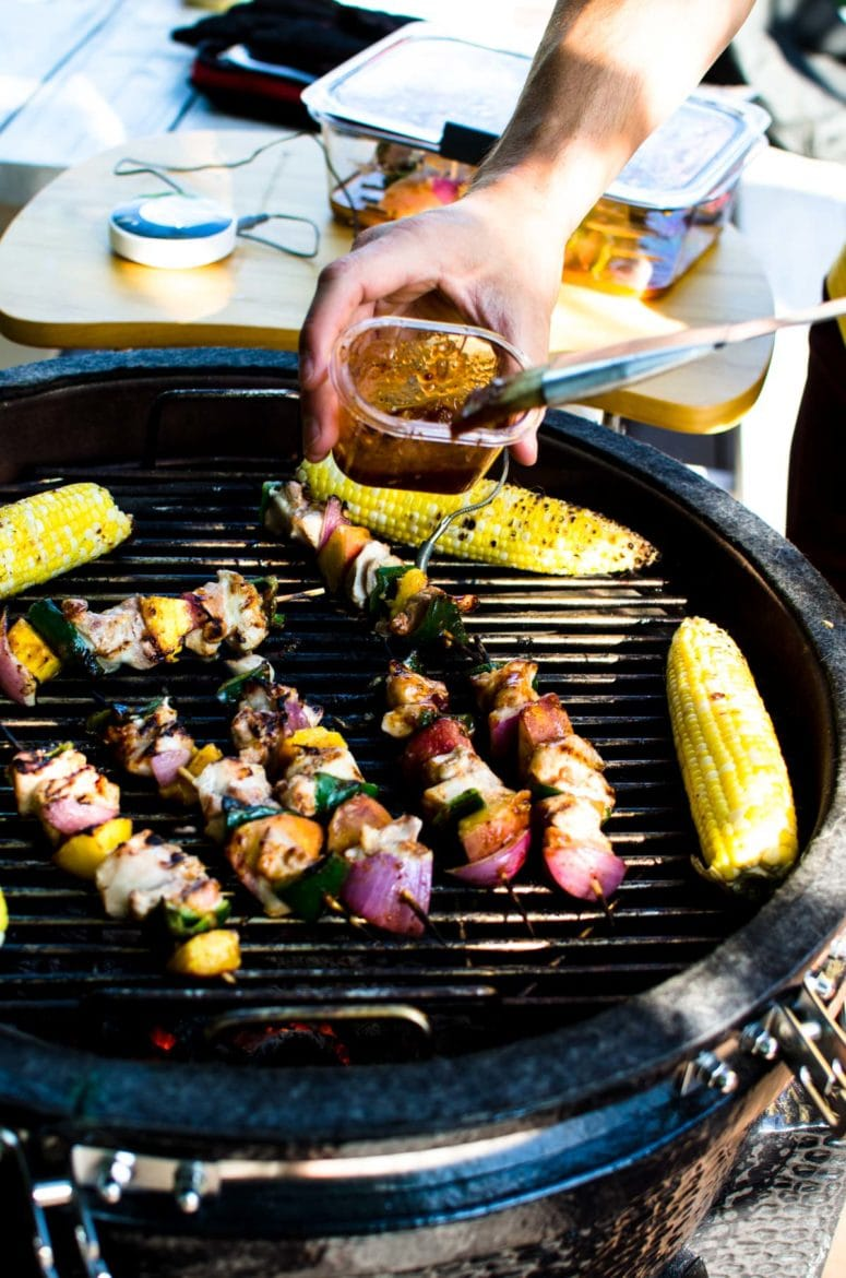 An open grill with peach bbq chicken kabobs and grilled corn on the grill grates.