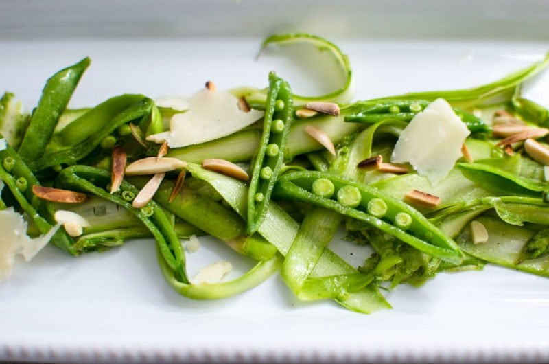 Shaved Asparagus and Sweet Pea Salad with Lemon Vinaigrette on a serving dish.