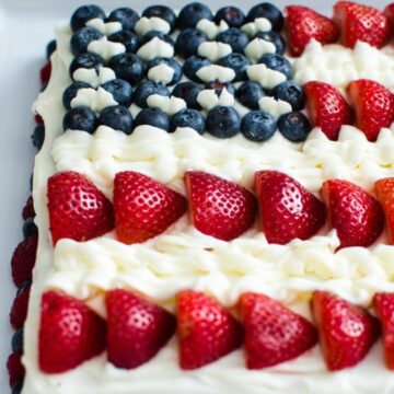 This fresh berry flag cake is made from scratch and is moist, flavorful, and perfect to serve for the 4th of July or Memorial Day! It's decorated with loads of berries and cream cheese frosting!