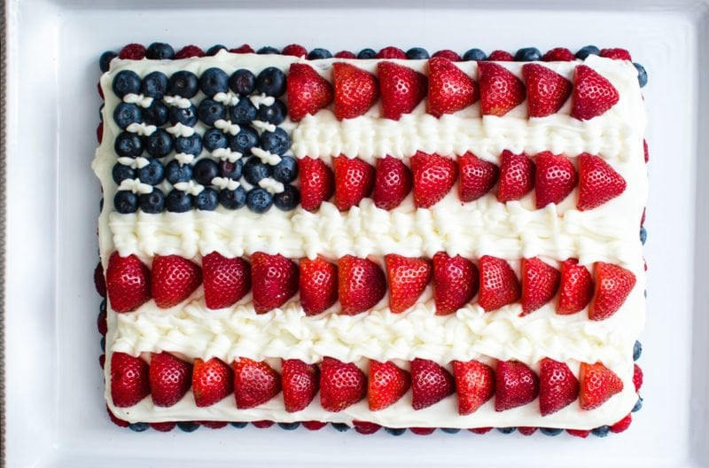 American flag cake made with berries and cream cheese frosting.