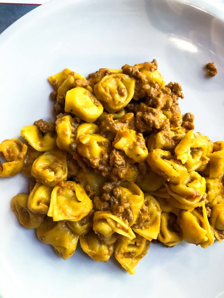 A plate of fresh tortellini with meat sauce.